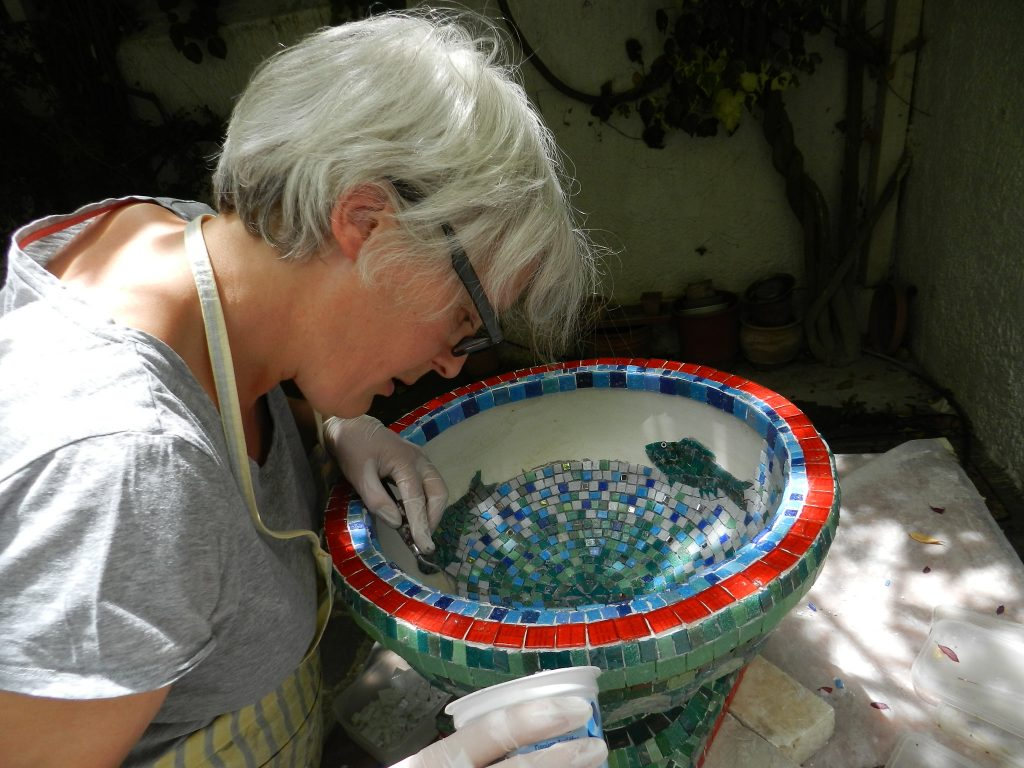 mosaic artist making a garden urn mosaic decorated with vitreous glass