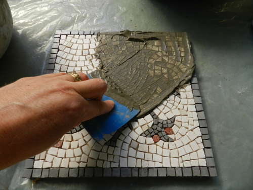 Apply the grout to the mosaic with a spreader tool.