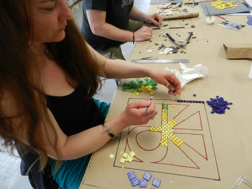 Chicago Mosaic School: student works on a mosaic logo