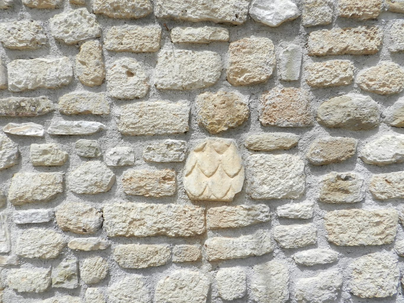 Village house wall with recycled stone, Corinth, Greece.